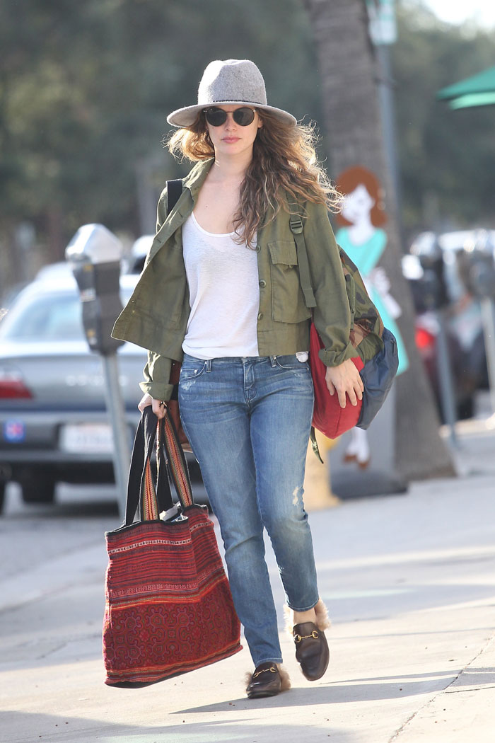 rachel Bilson jeans and a white tee paired with an olive green jacket, grey floppy hat, and Gucci fur loafers
